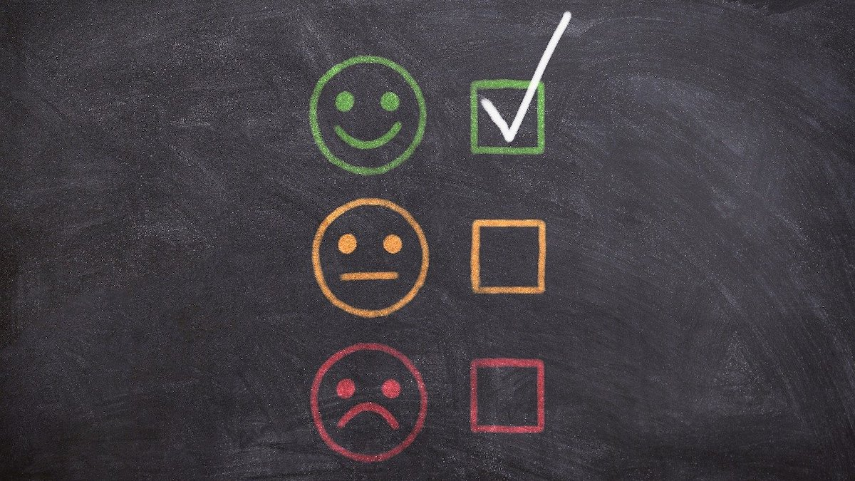 chalkboard with color-coded faces included one green smiley face with a check mark next to it, a yellow unsatisfied face and a red angry face.