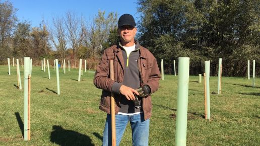 Doug Hershey standing in a field of tree tubes