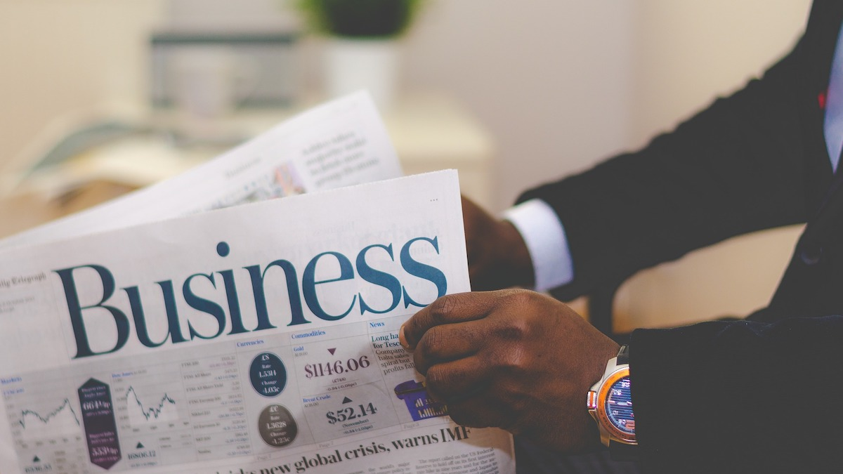 Man holding business section of a newspaper