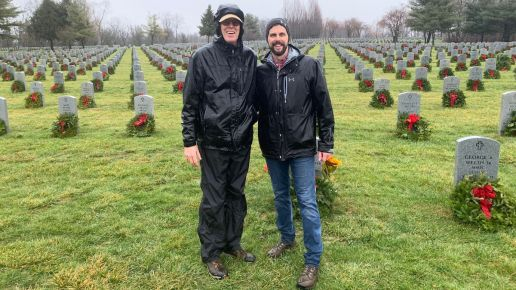 Kevin Murphy and his dad standing in front of a cemetery with freshly laid wreaths