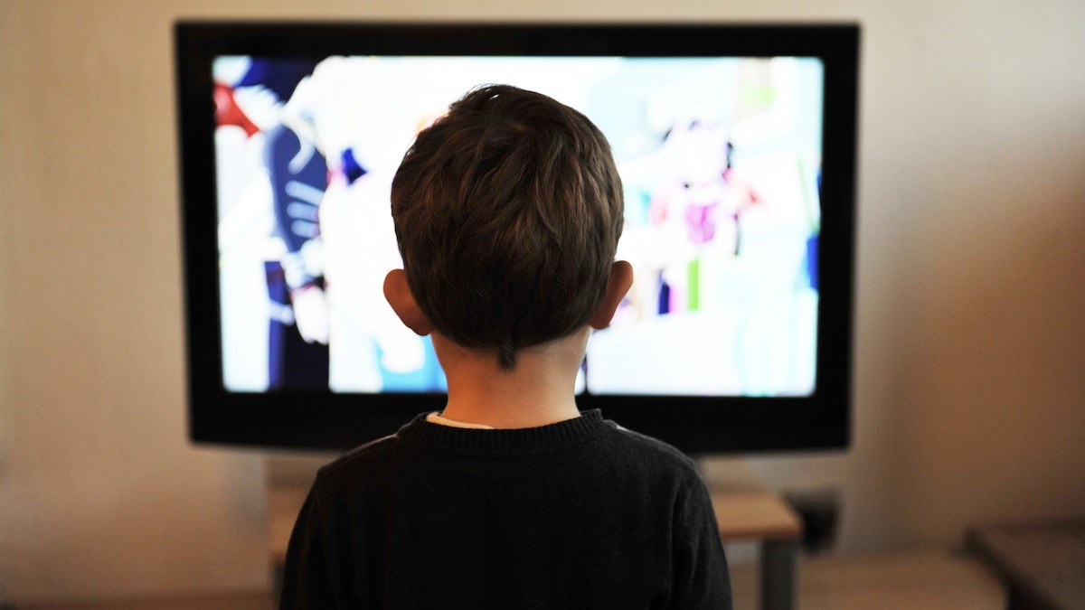 Child sitting in front of a TV screen
