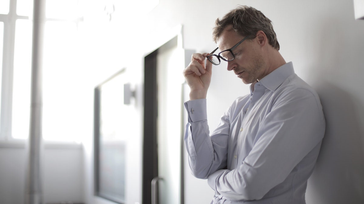 Businessman taking off glasses in frustration