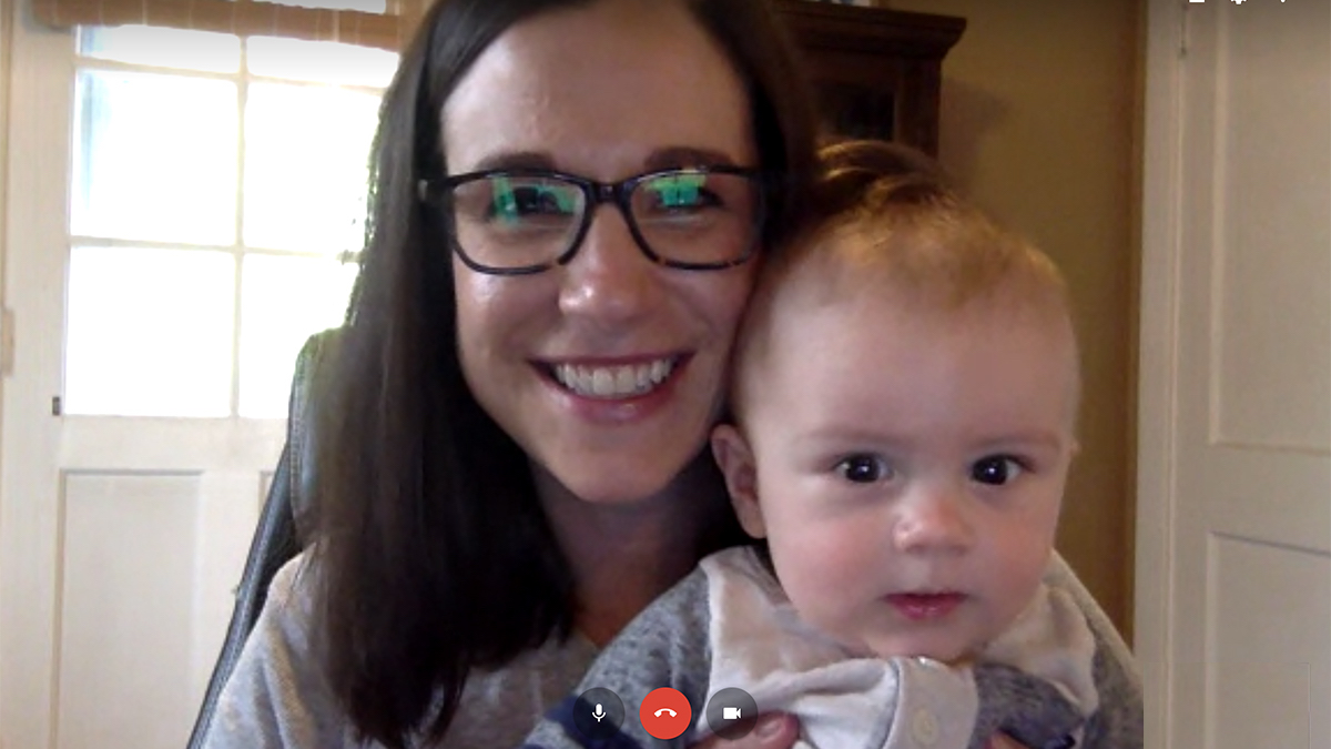 Woman holds her baby while on a video chat