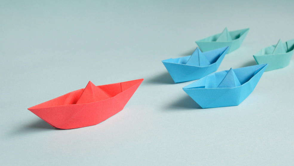 Proactive origami boat leading other boats in a race