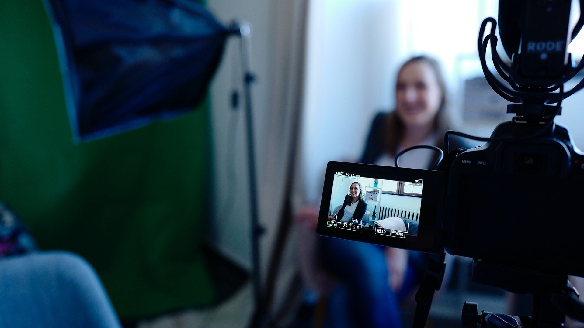 Picture of a woman being filmed from behind the video camera and monitor